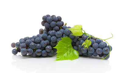 dark grapes and green leaves closeup on white background