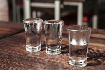 Three frozen shot glasses of vodka on a wooden table.