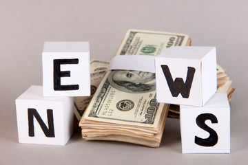 """White paper cubes labeled """"News"""" with money on grey background"""