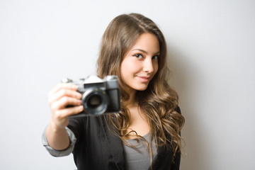 Brunette beauty holding vintage camera.