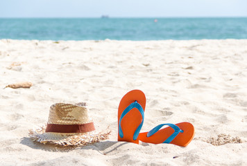 flip-flop and a woven hat on the beach.