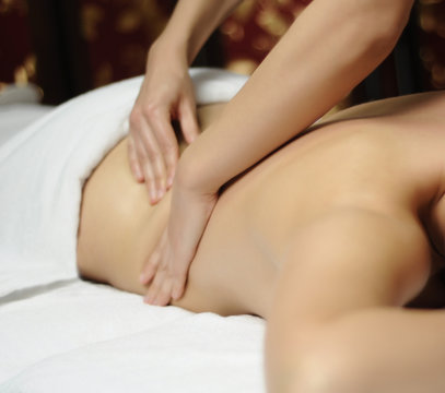 Professional woman masseur doing massage to female client in spa salon