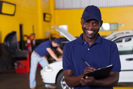 african american male vehicle mechanic writing report