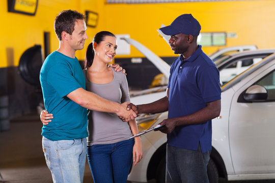 auto technician handshaking with couple