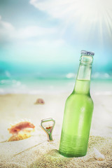 Ice cold bottle of lager or soda on a beach