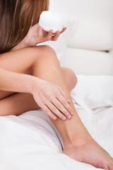 Woman Applying Lotion On Her Feet