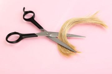 Pieces of hair cut with scissors on pink background