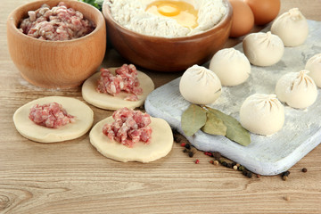 Raw dumplings, ingredients and dough, on wooden table