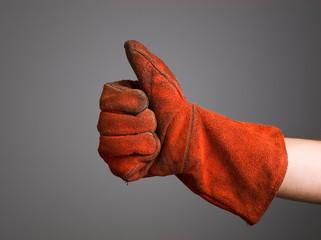 Hand expressing positivity with welder glove