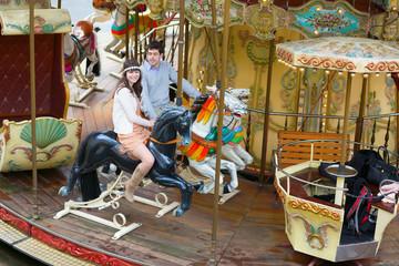 Couple having fun on a merry-go-round
