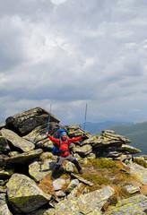 Happy hiker against stones.