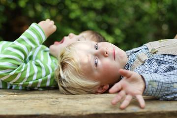 zwei jungen liegen im garten