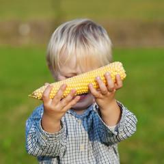 kleiner junge mit maiskolben