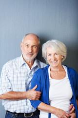 älteres ehepaar vor grauer wand