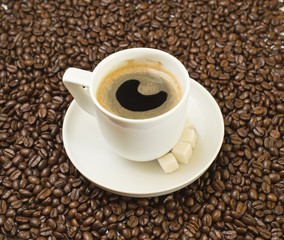 Cup of black coffee over bean covered background