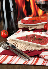 Tasty salami on plates on wooden table on fire background