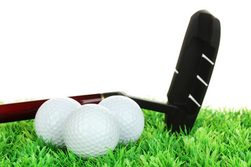 Golf balls and driver on grass isolated on white