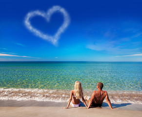 love concept - young couple on sea beach look at cloud heart