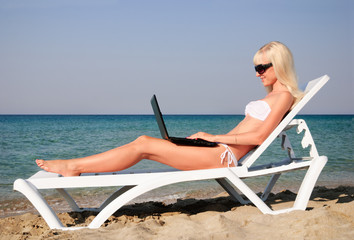 Cute blonde woman with white laptop on the summer beach