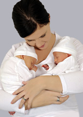 Young mother with twin babies in white clothing