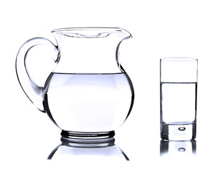 Glass jug and tumbler with water on white