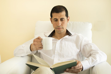 relaxed man reading a book and drinking