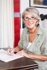 seniorin löst ein kreuzworträtsel