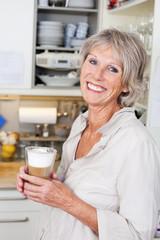 moderne seniorin genießt cappuccino zu hause