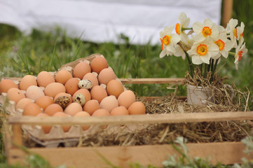 in a wooden box with straw tray with eggs and flowers