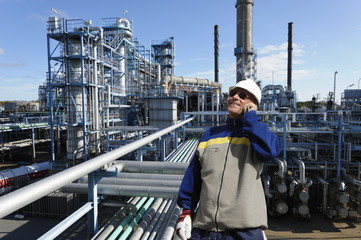 oil worker with large refinery in background