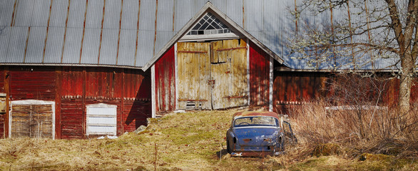 old vintage car-wreck parked in front of a barn