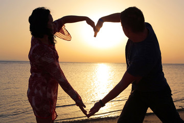 Couple making romantic heart shape at sunrise on the beach