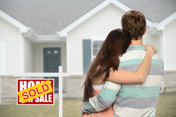 Couple inf Front of Home with Sold Sign