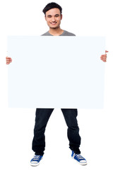 Handsome guy holding blank ad board