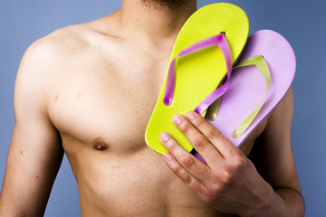 Close-up of man holding flip-flops