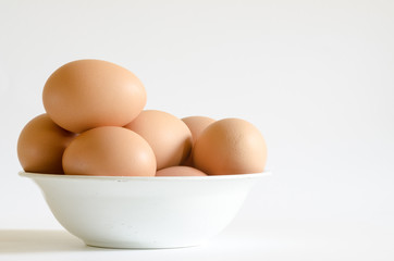 a pile of eggs on old white bowl
