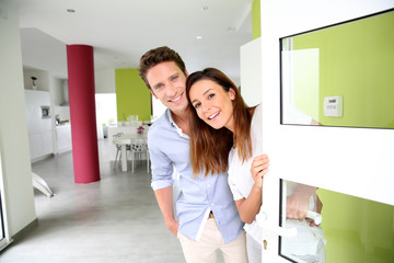 Wall Mural - Cheerful couple inviting people to enter in home