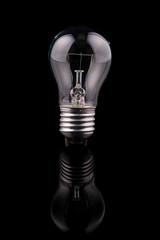 Light bulb on black background, reflection