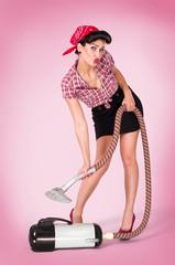 Pinup zeigt Hausfrau mit Staubsauger beim staubsaugen