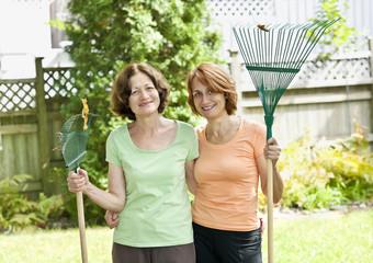 Women with rakes in garden