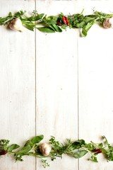 Frame of herbs on white wood background