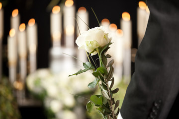 Grief - man with white roses at urn funeral Wall mural
