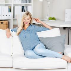 entspannte frau sitzt auf dem sofa