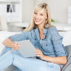 entspannte frau mit tablet zuhause auf dem sofa