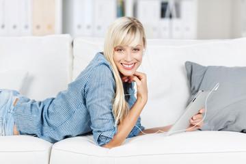 lächelnde frau liegt mit tablet auf dem sofa