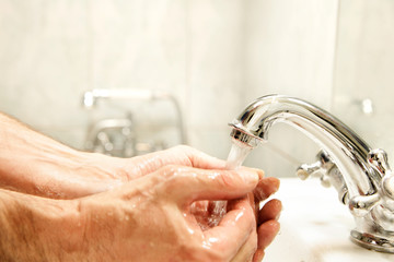 Washing hands in washbasin. Focus on faucet
