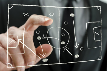 Coach pointing to a football strategy plan
