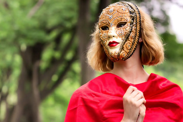 Blond woman in carnival mask over foliage background