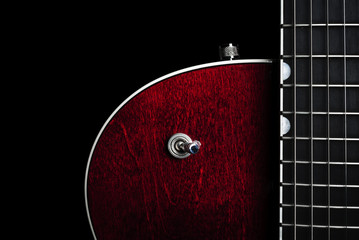 Shiny and sleek red electric guitar again a black back drop