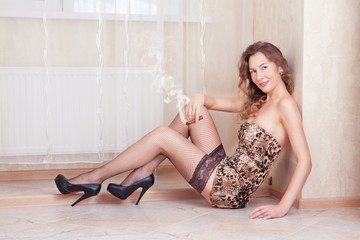 Cute woman lying on the floor smoking a cigar stockings and leop